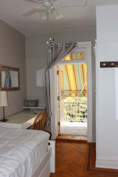 Your bedroom with the door to your personal balcony open, and the awning stretched out for shade.
