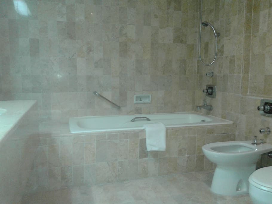 Large marble bathroom with tub and bidet.