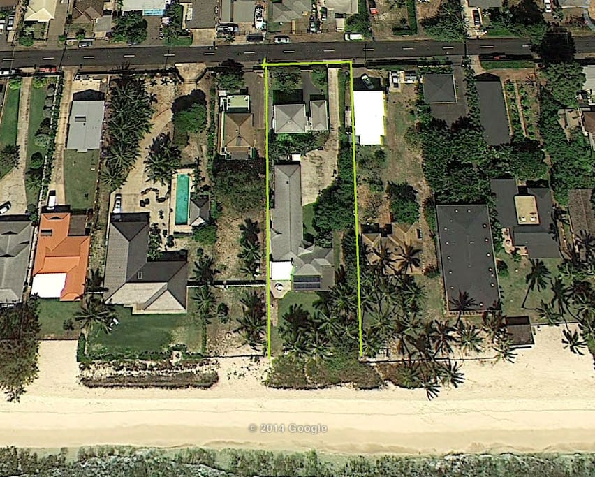 Aerial view of the entire property and layout in relation to the beach. The property is outlined in yellow, with the guesthouse in the upper portion of the lot.