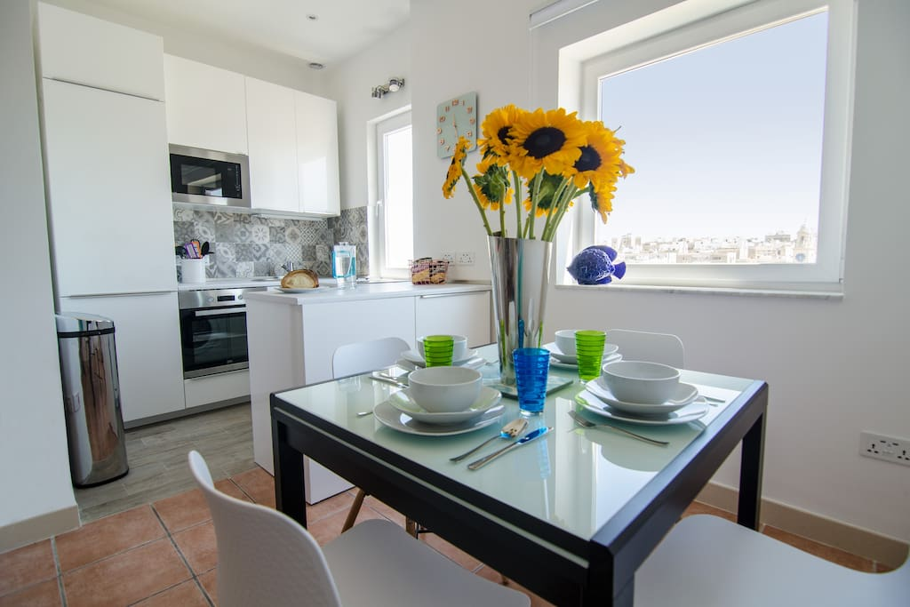 A bright open kitchen and dining area with views of the waterfront and over to Fort St. Angelo.