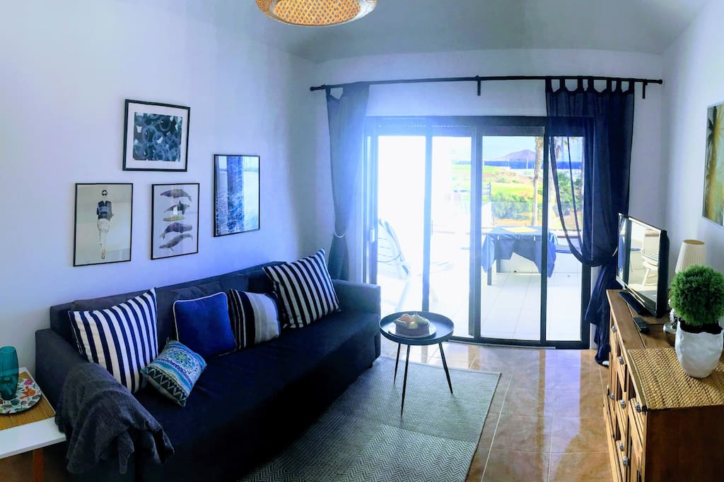 Living room with terrace and stunning view towards the ocean, marina and golf yard