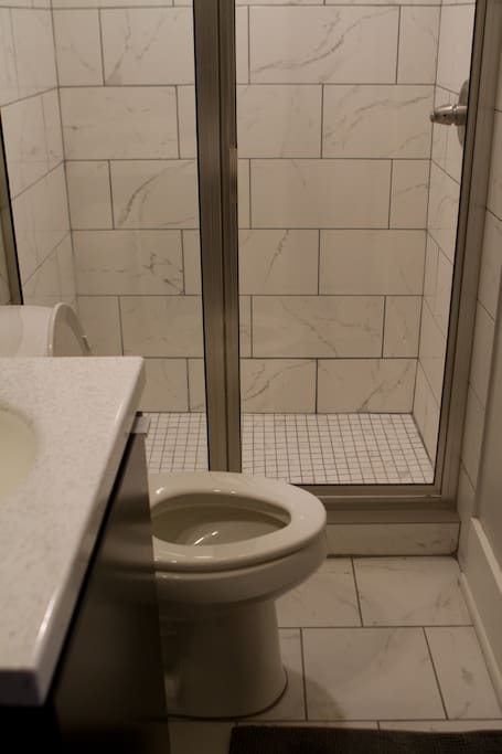 Newly renovated, clean bathroom with shower.