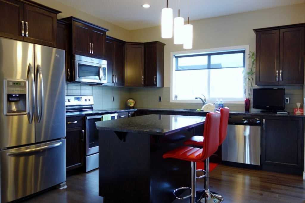 Kitchen, stainless steel appliances, granite counter tops. Pocket office off to the right of photo.