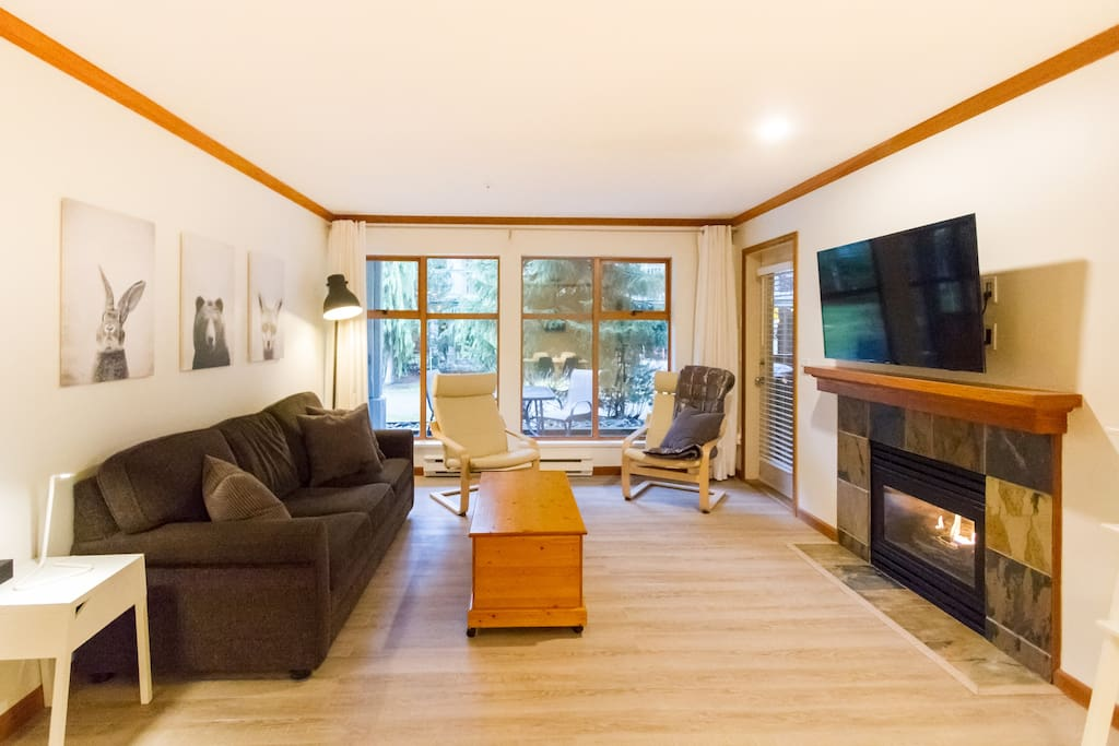 Living room with large windows, patio door and beautiful gas fireplace.