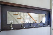 Repurposed piano piece for entryway mirror and coat rack