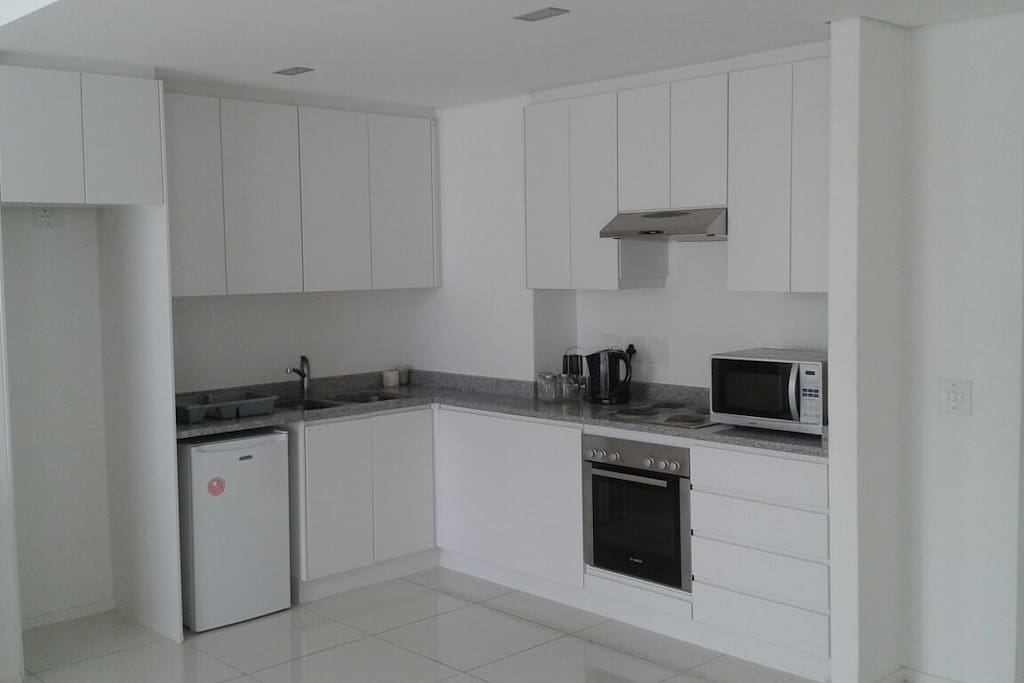The kitchen is equipped with a microwave, a kettle, a bar fridge, an oven and stove. Cutlery, crockery and a few pieces of cooking equipment are available too. There is also an ironing board and an iron.