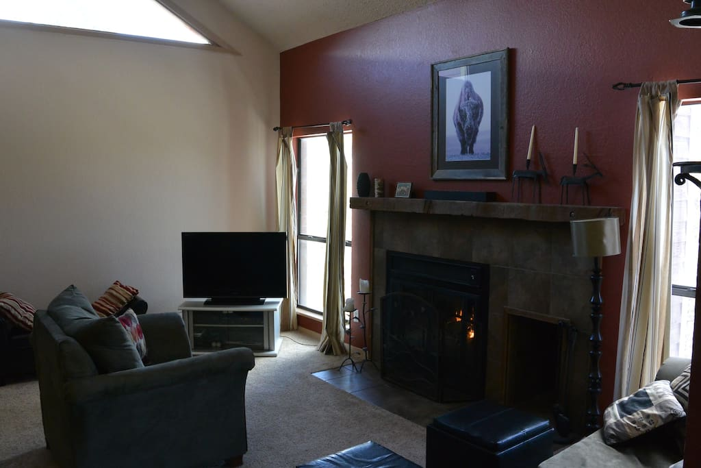 Living Room with lots of natural light, view of the mountains, and a gas fireplace. (TV has been updated to a wall mounted flat screen, updated photo to come)