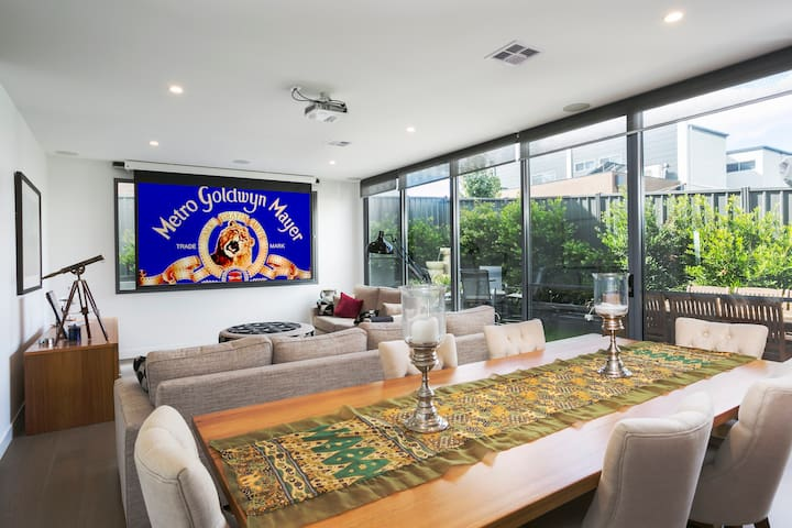 Combined dining /lounge with projection screen and TV looking out to a lovely court yard