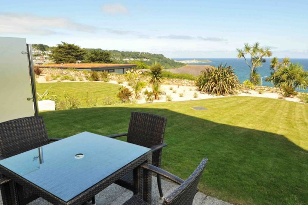 Private front dining terrace which then opens onto a shared grass lawn with sea views