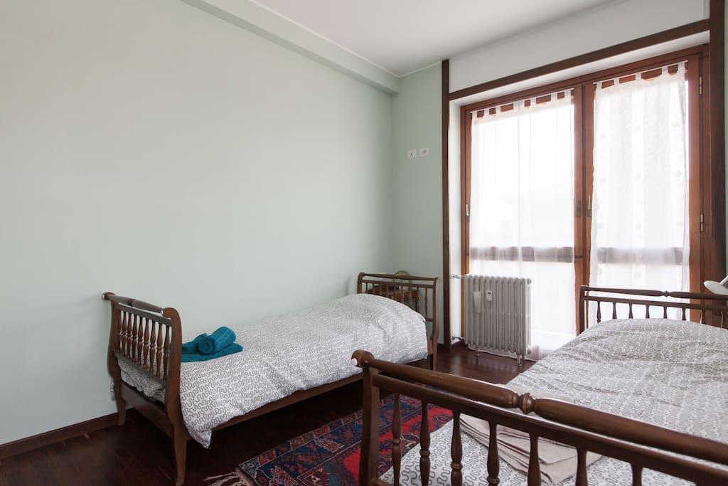 Prima camera con doppia esposizione  e balcone, 2 letti singoli o letto matrimoniale, comodini e armadio d'epoca, aria condizionata, parquet