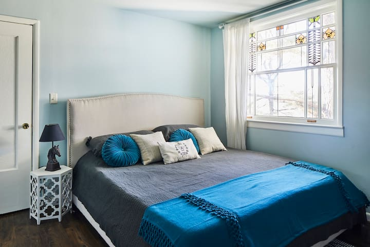 The soothing master bedroom showcases an antique stained glass window. You'll feel well rested after a night in the king size memory foam bed.