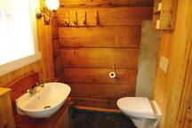 The bathroom is small but functional with shower, sink, toilet and clothes washing machine. There is heating in the floor.