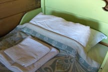 The green living room bed with bed linen and towels