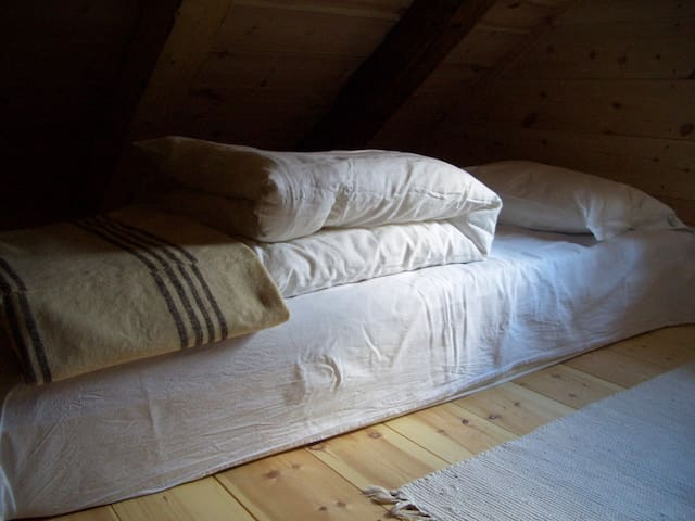 One of the sleeping loft beds (2x200x75 cm) with bed linen and an old handwoven blanket.