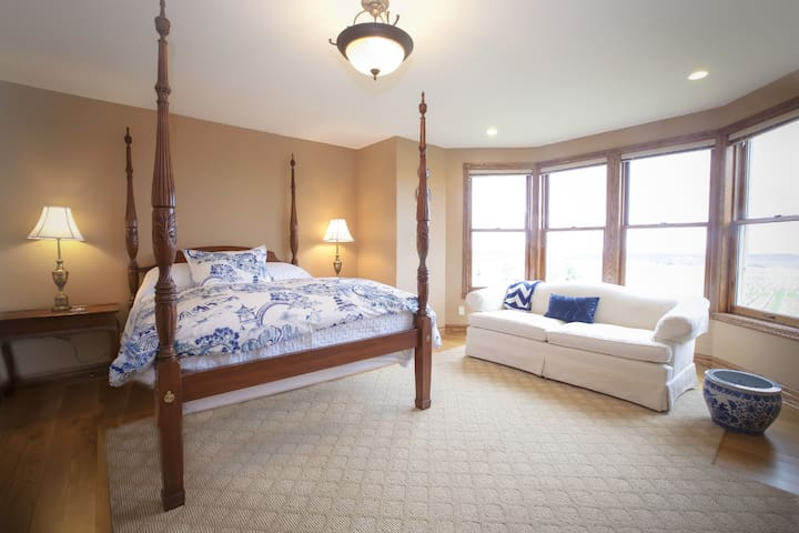 Master Bedroom with four poster queen bed and a reading sofa
