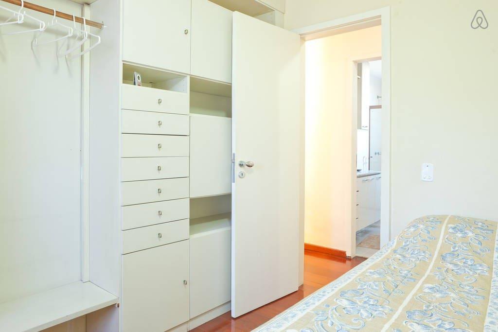 A wide closet with many doors with hanger clothes, drawers  to keep your belongings. Armário  com gavetas,  portas e espaço para guardar e pendurar  seus pertences.