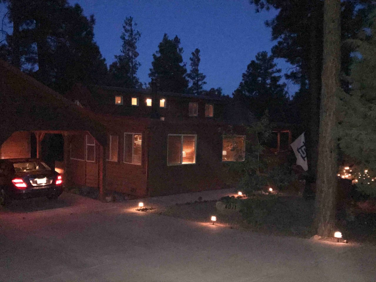 Night time the cabin glows with mood lighting in the garden and surrounding area