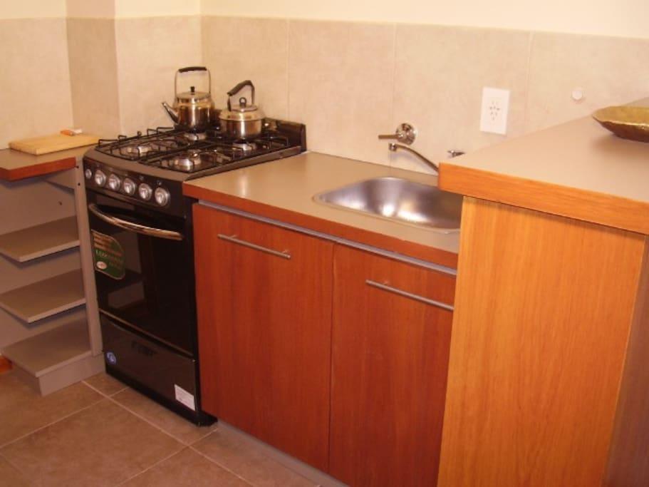 cocina con horno a gas y microondas y heladera