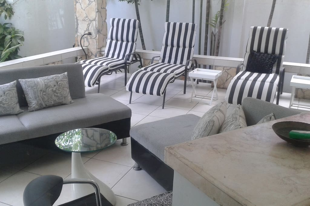 Outside living room with chase lounge chairs and a bartop