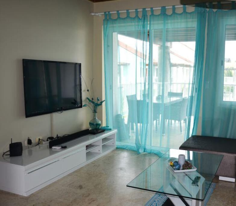 Living quarter with entertainment center and patio doors to spacious covered balcony