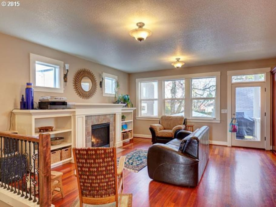 Living room with gas fireplace, opening to rear deck with grill and seating for 10