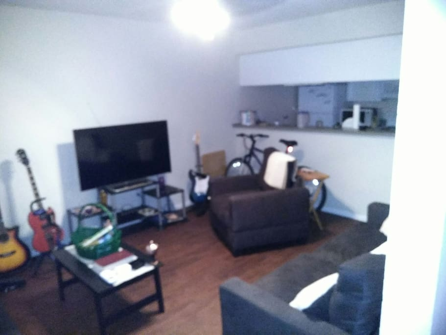 The living room area is fully equipped with a 60-inch smart TV a couch loveseat and chair