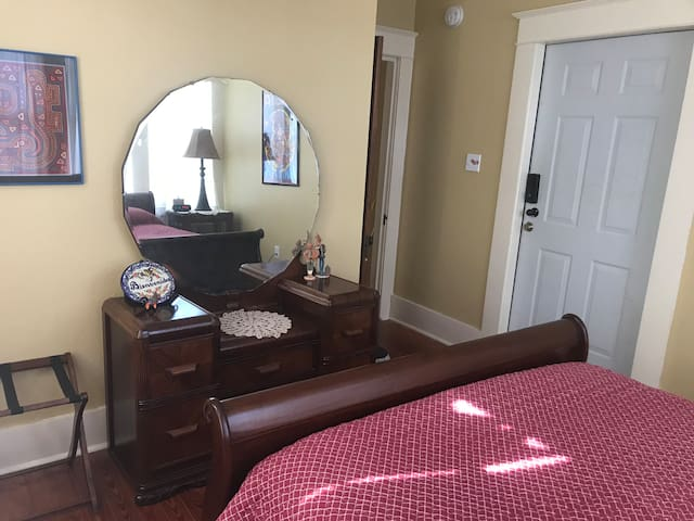 The private entry opens into the main bedroom. Luggage rack and dresser with mirror are provided
