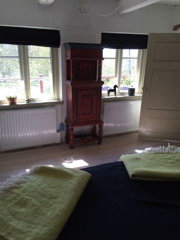 Sovrummet med två härliga dubbelsängar. Utsikt över lummig trädgård