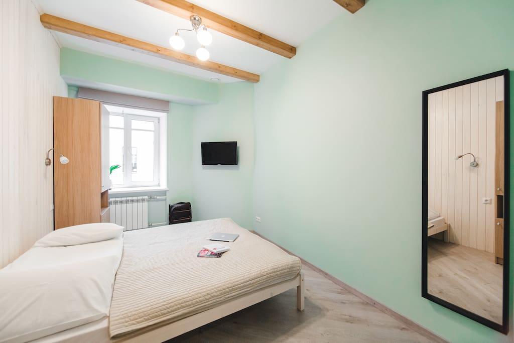 Общий вид номера. Зеркало, телевизор, удобные шкафы для верхней одежды, двуспальная кровать, журнальный столик.