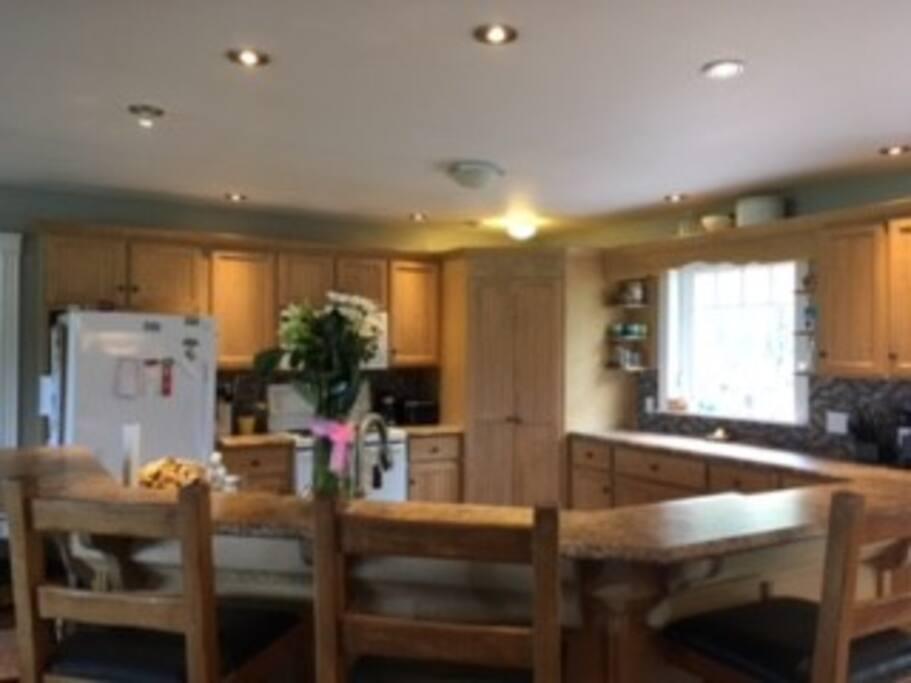 Open kitchen area, bar stools, spacious.