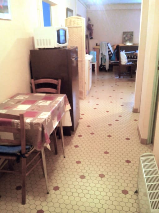 L'espace cuisine avec frigo, micro-onde, table et ses chaises, gazinière. Lavabo dans la pièce à côté.