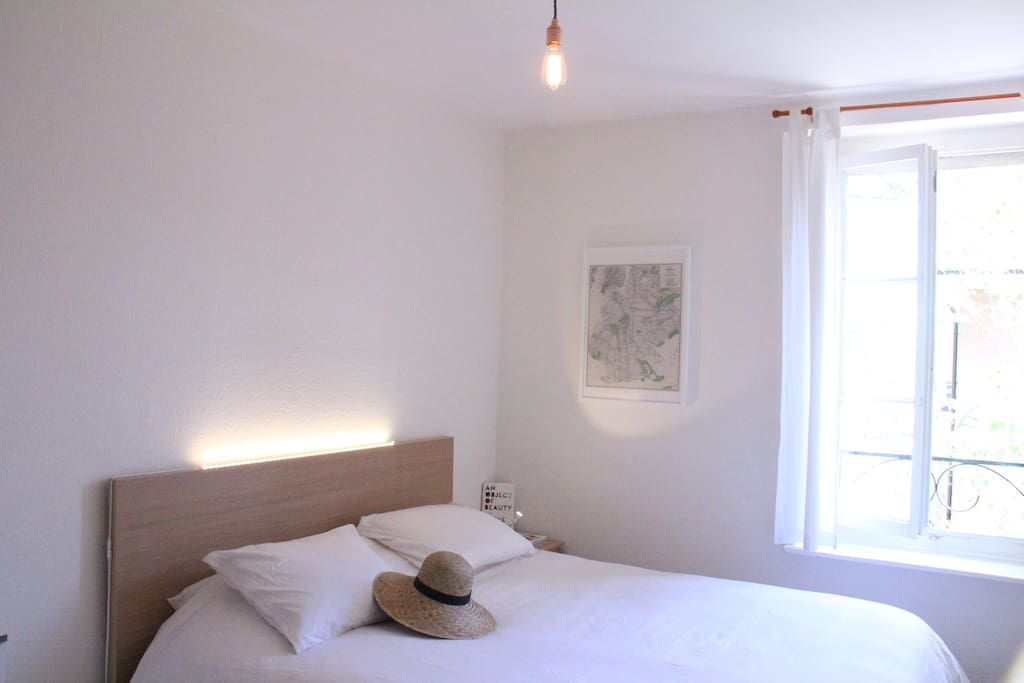 the bedroom with comfortable bed overlooking a pedestrian street