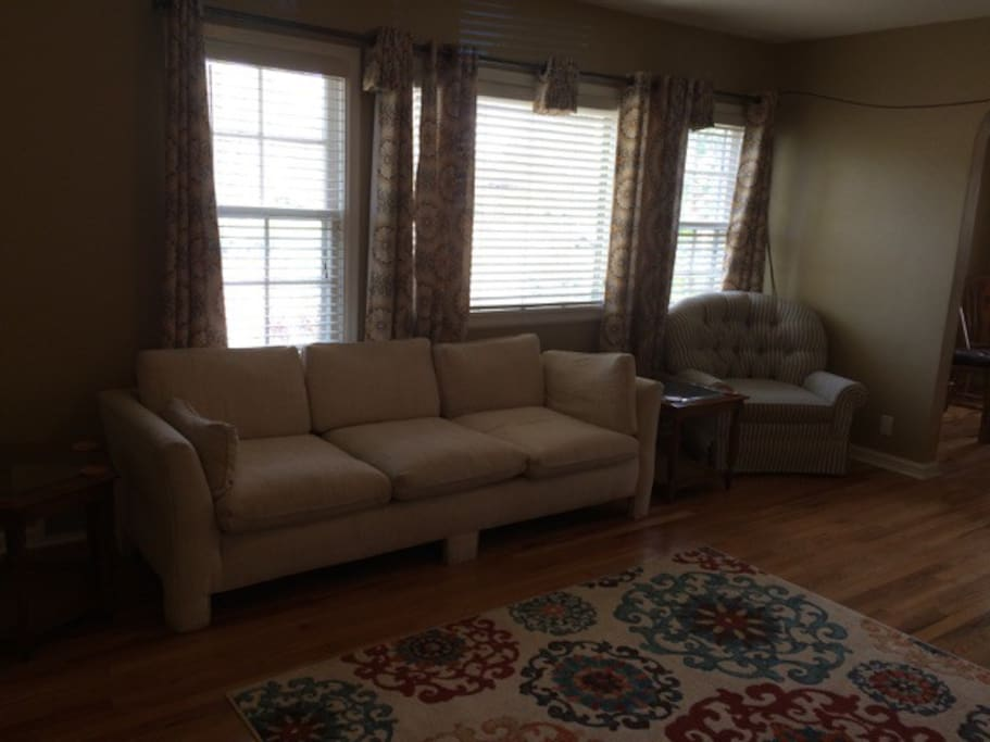 Hardwood floors, couch, chair, love seat, flat screen tv.