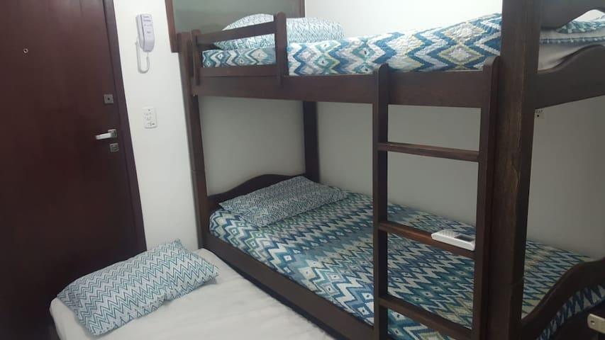 Quarto com beliche e uma cama auxiliar, ar condicionado e três travesseiros.