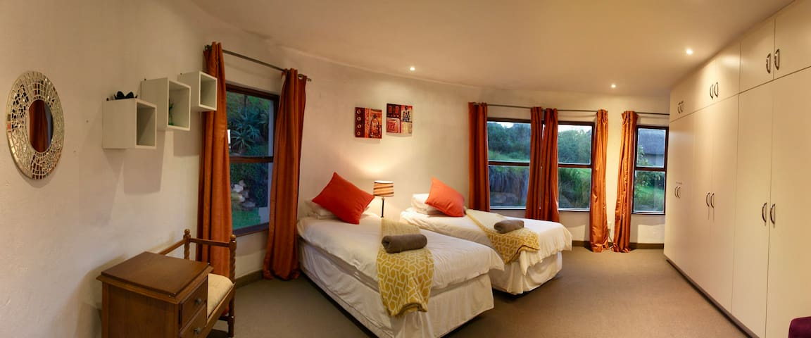 Spacious bedroom 4 with garden views and large shared bathroom.