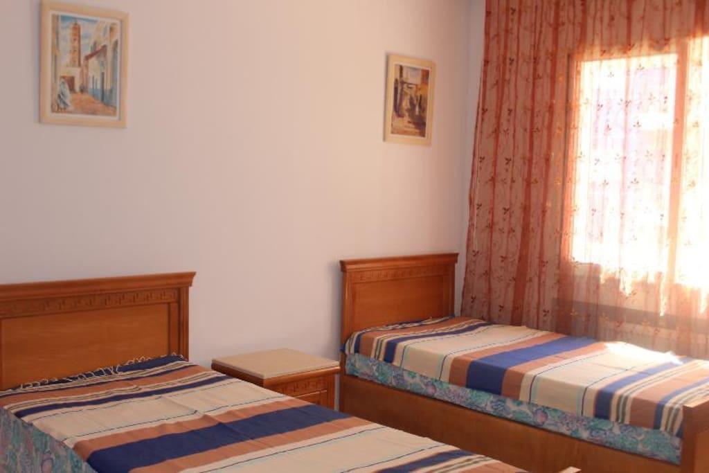 2ème Chambre avec deux lits une place, une coiffeuse et une armoire,  fenêtre donnant sur la piscine