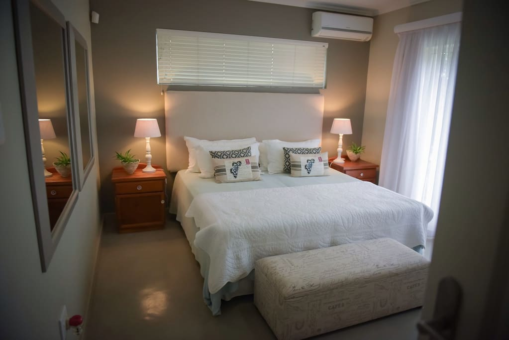 Main bedroom with standard King size bed, air-conditioning and ceiling fan