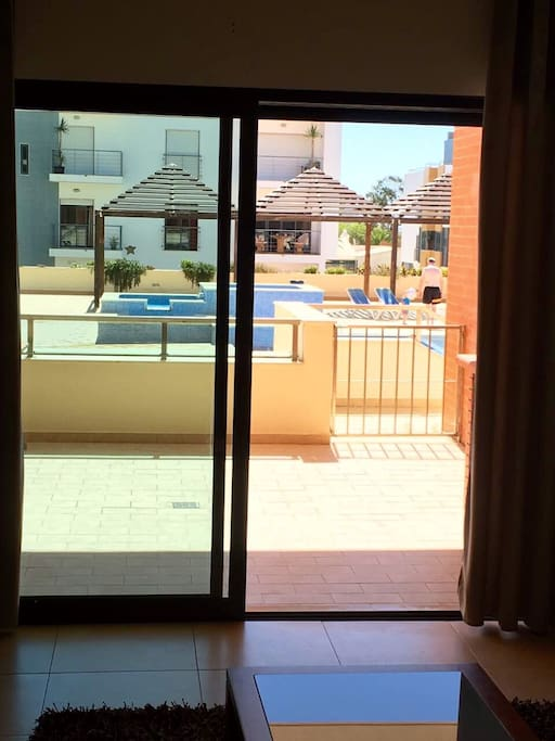 view of balcony and pool area from apartment