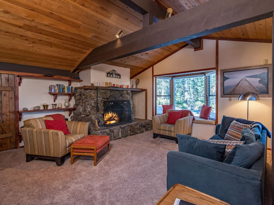 Wood-paneled vaulted ceilings and a wood-burning fireplace in the living area, professionally cleaned by TurnKey's housekeeping staff.