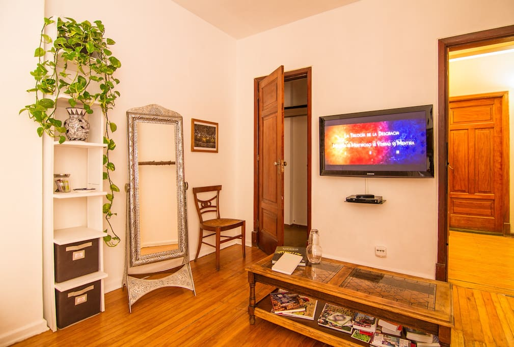 "Full length mirror, closet with clothes hangers, 42"" screen & Blu-ray/DVD player & center table with books regarding México."