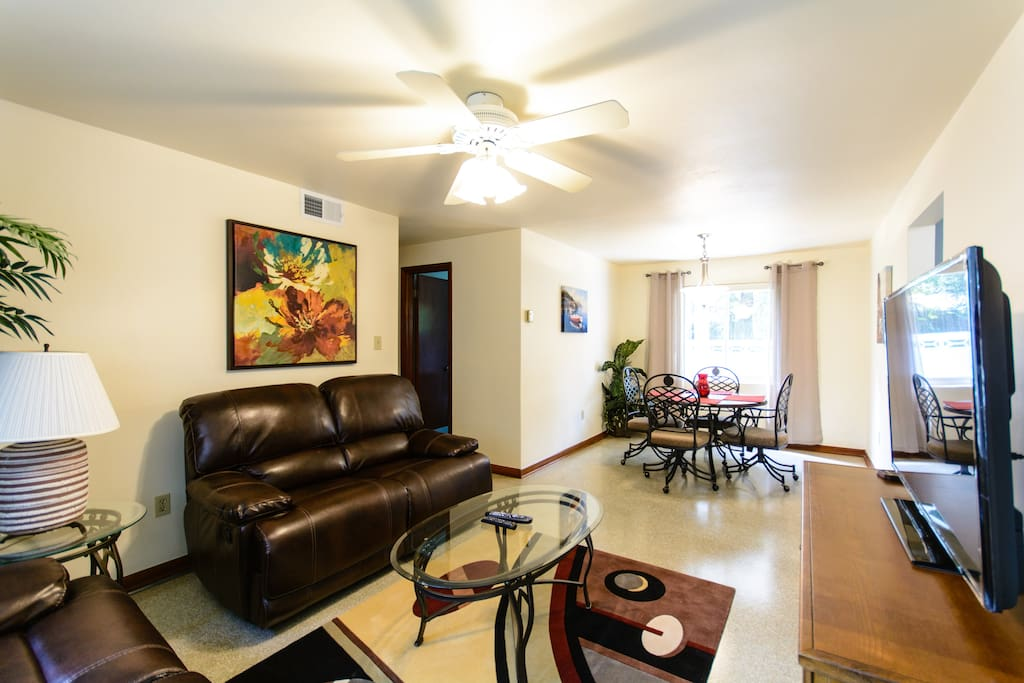 """Living Room showing one of two reclining love seats in front of 55"""" flat screen TV with dining area at west window.  Terrazzo floors."""