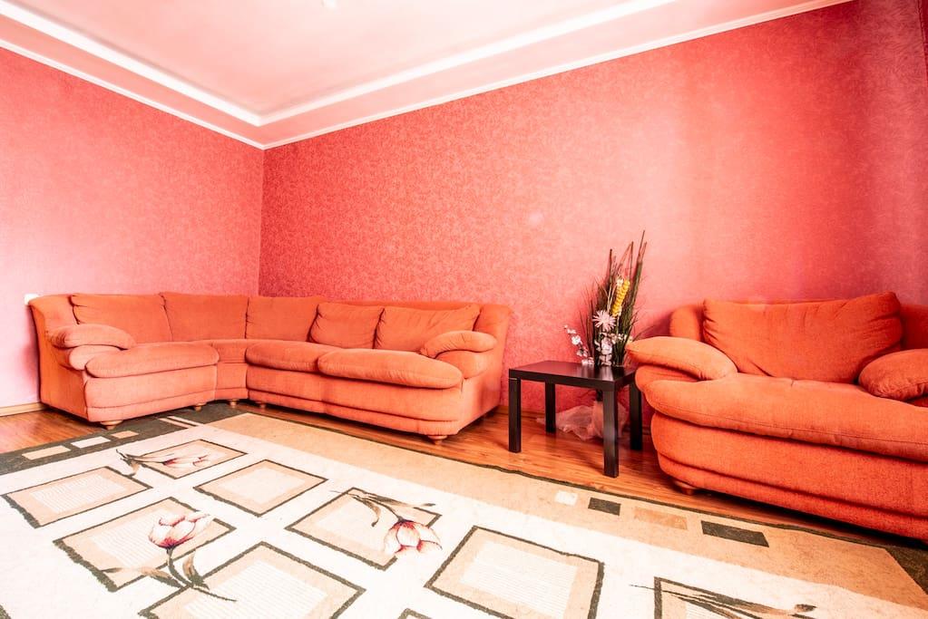 Комфортная и уютная гостиная комната с телевизором и диван-кроватью