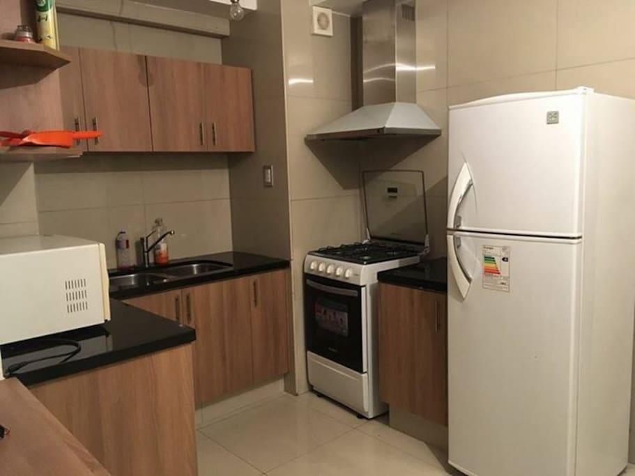 Cocina, con extractor de grasa, microondas, heladera, cocina 4 hornallas, utensilios de cocina, muebles de cocina