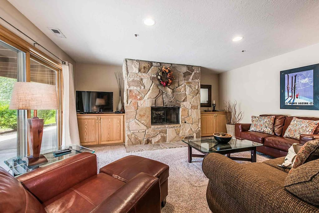 """Open concept living area features comfortable leather and fabric furnishings, 42"""" HDTV with Comcast TV and floor to ceiling stone fireplace."""