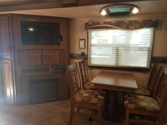 Dining area for 4 with a propane fireplace and a flat screen tv with surround sound.