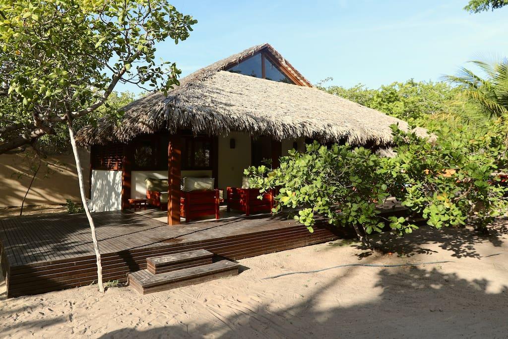 Bangalô com sala de tv, cozinha, dois banheiros, varanda e deck com piscina