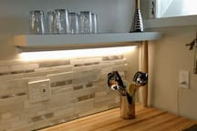 butcher block countertop, stone backsplash