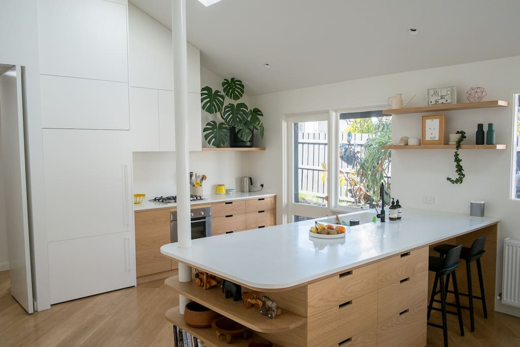 Our large kitchen, fully stocked with appliances and conveniences, in the large pantry (not shown) you'll find the microwave, Nespresso and SodaStream. Also there's a Sonos by the bar stools on the end of the massive island bench.