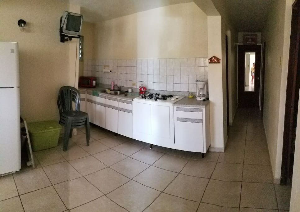 Kitchen area, stove, Fridge, sink and microwave.