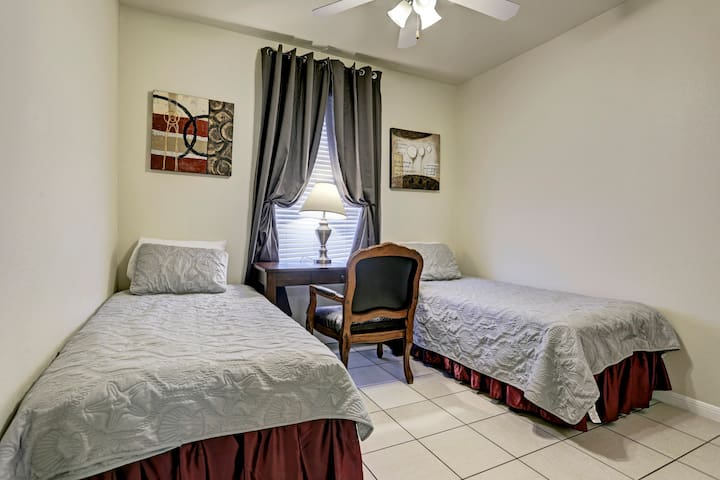 2nd bedroom, two twin beds. Nice working desk. Room darkening draperies. Modern paintings. Ceiling fan with three lights.  Tile floor. Nice and bright bedroom.